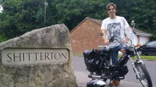 Paul Taylor with his moped next to the stone sign at Shitterton