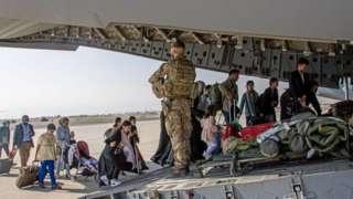 افغان شہری متحدہ عرب امارات جانے کے لیے طیارے پر چڑھ رہے ہیں