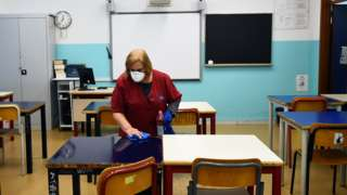 Cleaner in empty classroom in Turin, 2 Mar 20