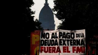 "Demonstrators hold a banner that reads ""no to foreign debt payment, IMF out"""