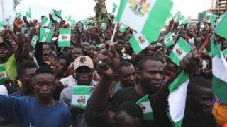 People waving Nigerian flags