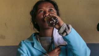 A student drinking Covid-Organics in Madagascar - April 2020