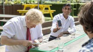 Prime Minister Boris Johnson (L) and Britain's Chancellor of the Exchequer Rishi Sunak (R) use their smartphones as they visit Pizza Pilgrims in West India Quay, London Docklands on June 26, 2020