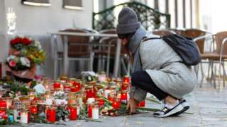 A woman places flowers at the site of a gun attack in Vienna, Austria, November 5, 2020