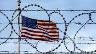 Bandeira americana por trás de uma cerca farpada na fronteira dos EUA com o México