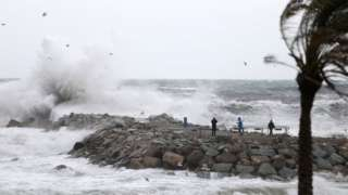 People look at huge waves battering a beach in Barcelona, Spain. Photo: 20 January 2020