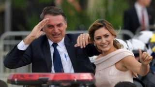 Brazil's President-elect Jair Bolsonaro (L) gestures next to his wife Michelle Bolsonaro as the presidential convoy heads to the National Congress for his swearing-in ceremony, in Brasilia on January 1, 2019
