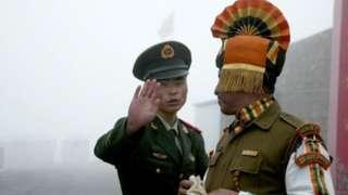 Soldado chinês gesticula enquanto fica perto de um soldado indiano no lado chinês da antiga fronteira de Nathu La entre Índia e China
