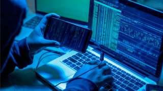 Hacker with computers in dark room.