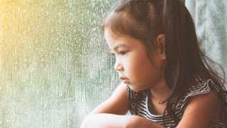 Menina olha pela janela