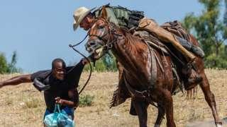 Border patrol agent grabbing man while on horseback
