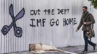 Homem passa em frente a grafite com palavras de ordem contra o FMI em fevereiro de 2015 em Atenas, na Grécia