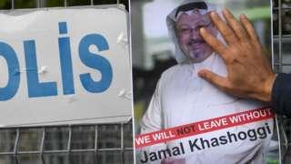 A man puts his hand over a poster of Jamal Khashoggi