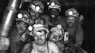 Black miner with white colleagues