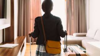 Woman entering hotel room with suicases