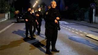 Cinco policiais enfileirados, o primeiro empunhando arma, em rua à noite