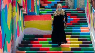 A woman, wearing a protective mask, walks down steps decorated with vibrant colours in Gaza City, on 3 May 2021