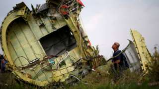 An investigator inspects the wreckage of flight MH17. File photo
