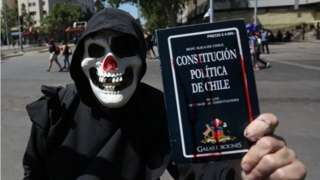 A man with a mask holds a Chilean constitution as demonstrators participate during a march at the Plaza Italia in Santiago, Chile, 18 October 2020.