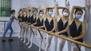Students wearing face masks take part in a ballet training session at Ballet Dance School Affiliated to Hainan Provincial Song and Dance Troupe on April 15, 2020 in Haikou, Hainan Province of China.