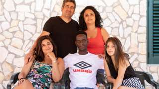 """Mohamed """"Lexy"""" Sanneh (au centre) entouré par les membres de la famille Ferraro, sa famille d'accueil"""