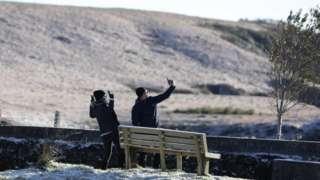 Casal tirando fotos em local com neve em Santa Catarina