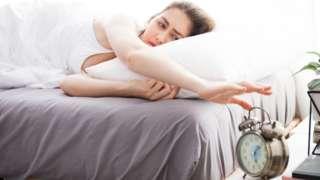 A woman turning off an alarm clock