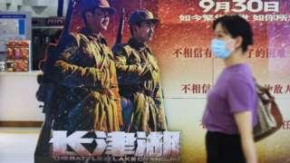 杭州一家電影院門前,一位行人走過大片《長津湖》的海報