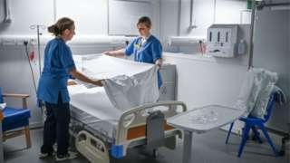 Hospital staff re-make empty bed
