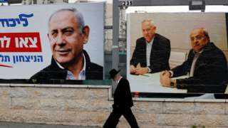 Man walks past election campaign posters in Jerusalem (file photo)