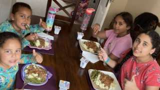The Andu sisters enjoying a meal made with their food hamper