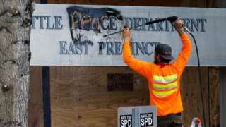 A worker removes graffiti off a police precinct sign