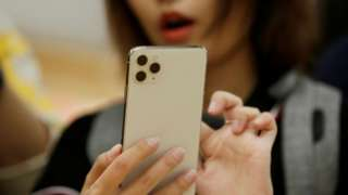 Một phụ nữ dùng iPhone 11 Pro Max ở Bắc Kinh