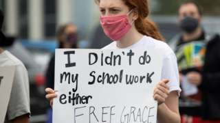"""Student holds up a sign saying: """"I didn't do my schoolwork either. Free Grace""""at a rally in the Detroit suburb of Pontiac on 16 July 2020"""