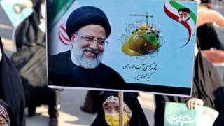 Uma mulher com lenço na cabeça e máscara segura pôster retratando Ebrahim Raisi e participa de um comício de campanha eleitoral na capital Teerã, em 14 de junho de 2021