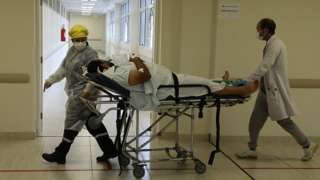 Profissionais de saúde transportam paciente em maca de hospital