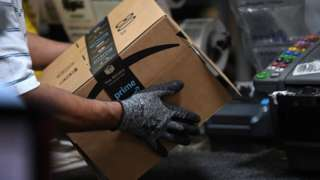 A worker handling a box from Amazon in a factory