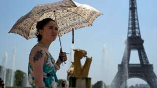 A woman cools down at the fountains of Trocadero, across from the Eiffel Tower, during a heatwave in Paris, France,