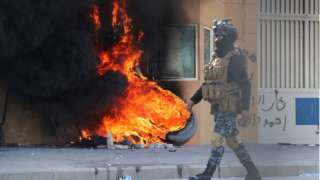 Iraqi security forces by burning tyres outside us embassy