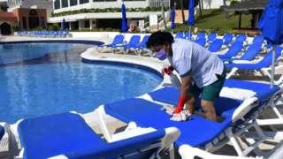 Trabalhadora com máscara limpa espreguiçadeiras no entorno de piscina de resort