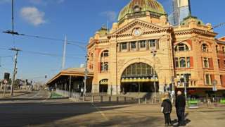 Two people stand in front of an otherwise deserted Flinders St Station in Melbourne