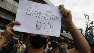 "Pro-democracy protester holds a placard with a message ""Free our friends"" as they gather for an anti-government protest at Kaset Intersection in Bangkok,"