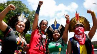 Four indigenous women raise their hands as they call for gender equality during a protest in Brasilia on International Women's Day, on March 8, 2020.