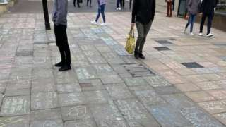 People walking and standing on High Street where there are chalk messages on the pavement