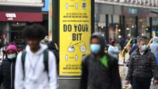 Shoppers wear facemasks as they walk along the streets of Manchester,