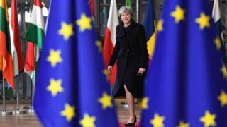 Theresa May standing between two EU flags