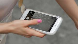 A woman holds an iPhone