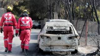 Members of the Red Cross search the area past burned cars after a fire in Mati, Greece, 24 July 2018