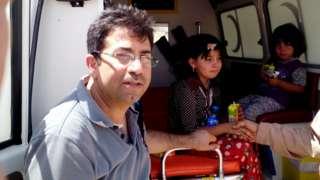 Mirza Dinnayi posa para foto em frente a ambulância em que atendeu a crianças yazidi
