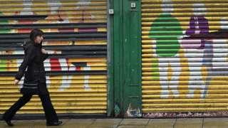 A woman walks past shop shutters in Sunderland